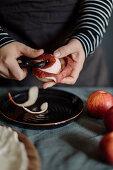 Woman peels a red organic apple