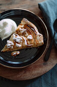 A slice of apple tart with a dollop of cream