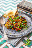 Vegan curry dish with lentils, zucchini, sugar snap peas and spinach