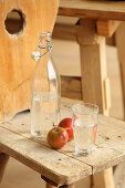 Apples and fresh water on a wooden chair