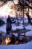 A woman hanging lanterns on a tree above a table laid in a snowy garden
