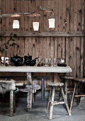 Antique wine glasses and black crockery on table in front of rustic board wall