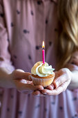 Woman in pink dress and blond hair holding with two hands a cupcake with a pink candle burning