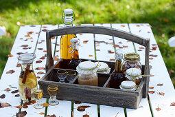 Wooden bottle carrier with apple jam, apple brandy, apple juice and apple cider