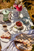 Cherry pie and coffee served outside on the table