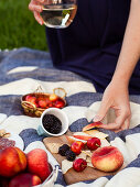 A woman holding a glass of white wine, reaching for a slice of peach, picnic with fruit and cheese