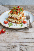Garden lasagna with zucchini cream, minced sunflower seeds, and tomatoes