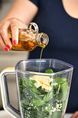 Pouring olive oil in food processor, making basil and arugula pesto