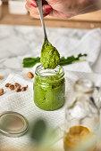Pouring homemade basil and arugula pesto in a jar