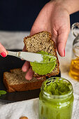 Spreading homemade basil and arugula pesto in a jar on a piece of bread