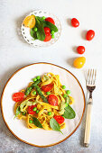 Saffron tagliatelle with green asparagus, peas and tomatoes