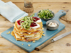 A stack of pancakes layered with Camembert, ham and cranberries