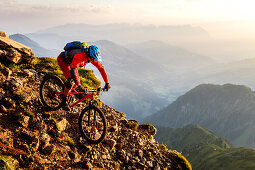 Middle aged man rides down a rocky and steep hiking path on his mountainbike, morning light, Wilder Kaiser mountain range in the background, Kirchberg, Tyrol, Austria