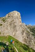 Mann und Frau beim Wandern vor Gipfel des Pizzocco, Belluneser Dolomiten, Nationalpark Belluneser Dolomiten, Venezien, Venetien, Italien