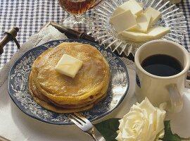 Pancakes mit Butter & Ahornsirup auf Teller & Tasse Kaffee