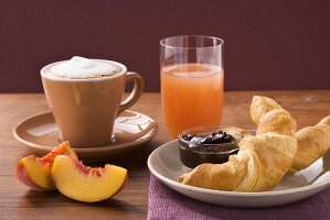 Croissant, jam, nectarine, cappuccino and grapefruit juice