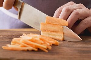 carrots being cut into fine strips
