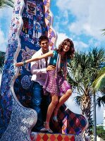 ausgelassenes Paar hat Spaß auf einer bunten Skulptur