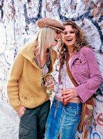 Frauen Kopf an Kopf, stehen dicht beieinander vor einer Mauer