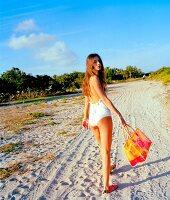 Frau in weißem Badeanzug, lange braune Haare, Sandweg, Tasche