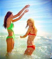 Zwei Frauen haben Spaß im Meer, Blondine und Brünette