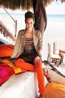 Frau sitzt auf Bett am Strand, Meer, Kamerablick, orange Hose