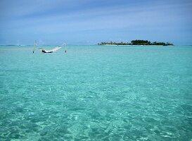 Person in Hängematte im Wasser, Insel Dhigufinolhu, Malediven