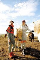 Two women wearing knitwear standing with icelandic horses in field, smiling