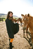 Happy brunette woman wearing poncho and scarf stroking icelandic horse and smiling