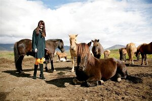 Brunette woman wearing poncho and scarf standing between many icelandic horses