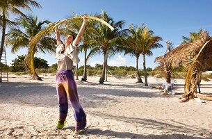 Frau steht im Sand, Batikhose, hält Palmwedel über Kopf, lacht