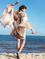 Rückansicht: Frau am Strand, Seiden- chiffonkleid weht im Wind, Arm hoch
