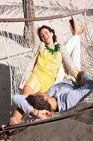 Mann und Frau liegen in Hängematte, lachen, Sommertag, Strand, Palmen