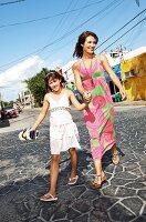 Strandmode: Mutter und Tochter in Sommerkleidern Hand in Hand
