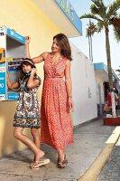 Strandmode: Mutter im Seidenkleid, Tochter im Baumwollkleid telefoniert