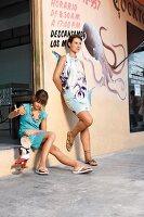 Strandmode: Mutter im Shirtkleid, Tochter spielt mit Marionette