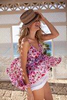 Frau mit Strohhut und geblümtem Sommerkleid