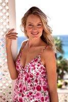 Frau in geblümtem Sommerkleid im Hintergrund Meer