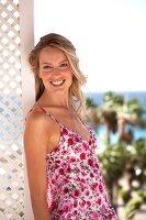 Frau in geblümtem Sommerkleid lächelt, im Hintergrund das Meer