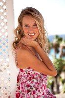 Frau in geblümtem Sommerkleid lächelt, eine Hand am Kinn
