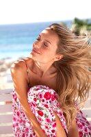 Frau im geblümten Sommerkleid hält, hält das Gesicht in den Wind