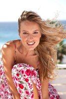 Frau im geblümten Sommerkleid lächelt in die Kamera