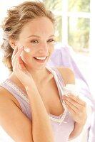 Frau mit blonden Haaren cremt sich mit Feuchtigkeitscreme ein
