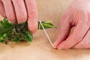 Tying herb stems together with kitchen twine