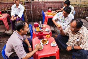 Enjoying samosas and tea in the street, Yangon, Myanmar