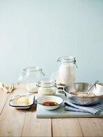 Zutaten für Plätzchen in verschiedenen Gläsern und Schalen, auf einem Holztisch