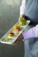 A chef presenting a mixed appetizer platter