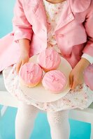 A girl dressed in pink holding a plate of pink cupcakes