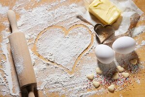 Various baking ingredients, a rolling pin and heart-shaped cutters