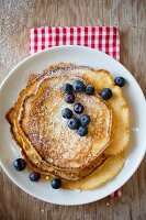 A stack of pancakes dusted with icing sugar